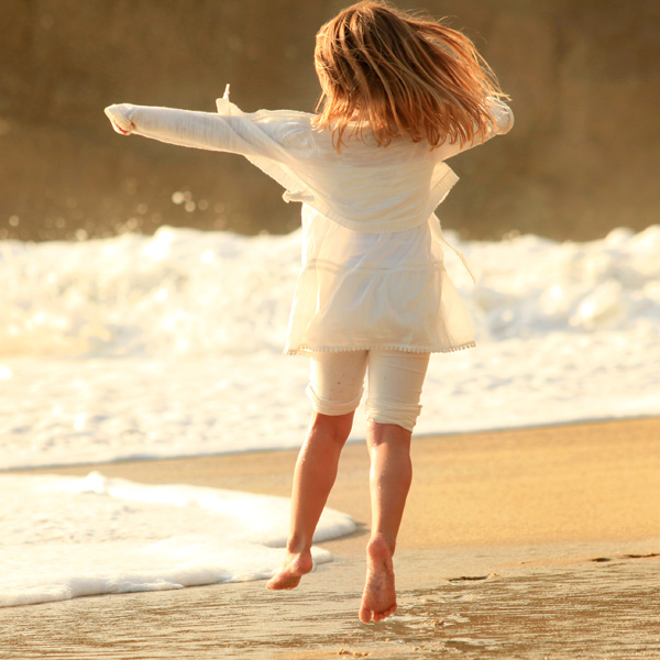 Young girl frolilcking on the beach