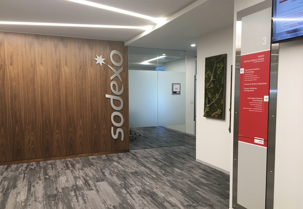 """Elevator landing with wayfinding and conference room """"wood"""" and 3D Sodexo logo."""