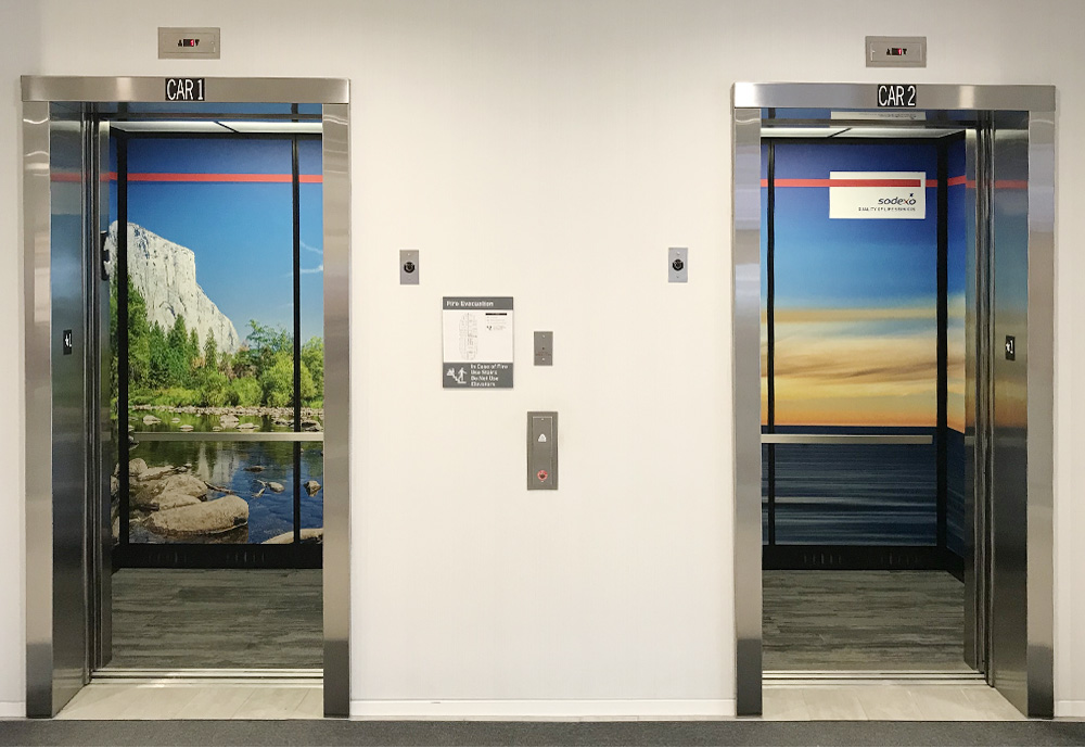 The elevators have their interior walls wrapped with vinyl graphics of images of Yosemite Valley and an ocean sunset.